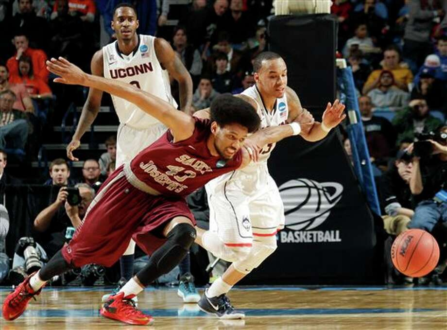 Saint Joseph's DeAndre Bembry (43) and Connecticut's Shabazz Napier, right, fight for control of the ball during the first half of a second-round game in the NCAA college basketball tournament in Buffalo, N.Y., Thursday, March 20, 2014. (AP Photo/Bill Wippert) / FR170745 AP