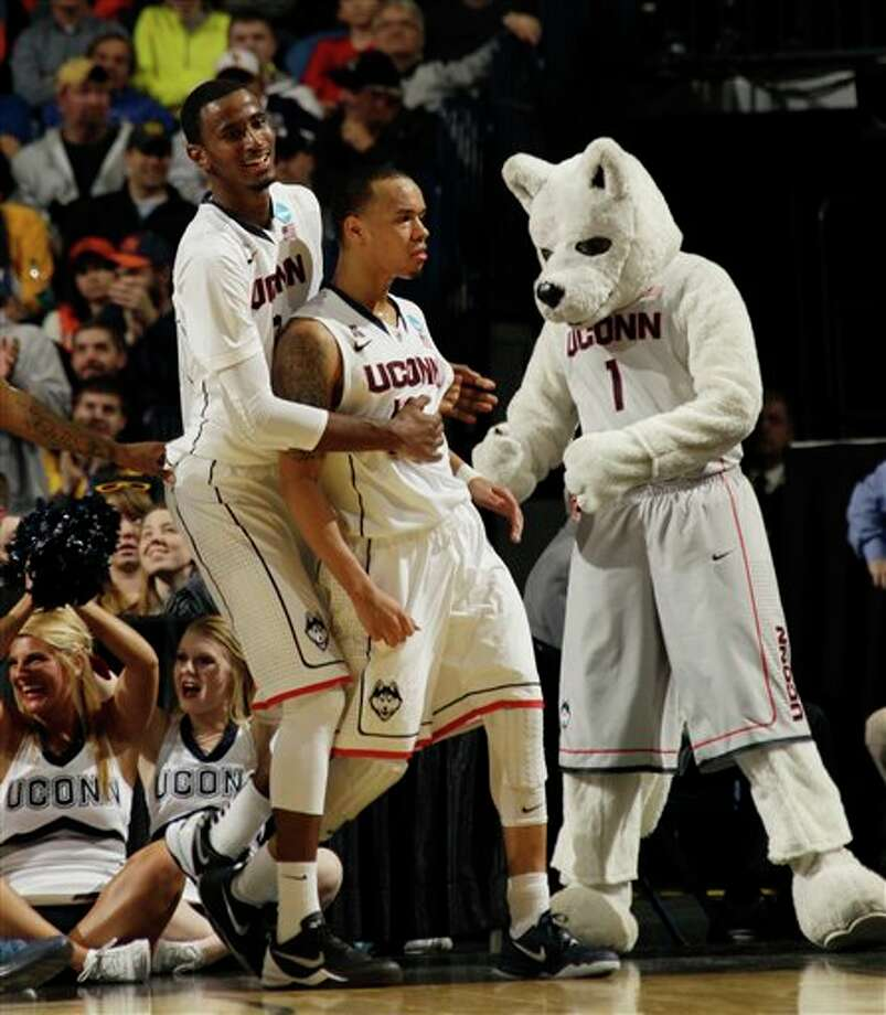 Connecticut's Amidah Brimah (35) grabs Shabazz Napier (13) after his basket alongside their Huskies mascot during overtime of a second-round game against Saint Joseph's in the NCAA college basketball tournament in Buffalo, N.Y., Thursday, March 20, 2014. Connecticut won the game 89-81. (AP Photo/Bill Wippert) / FR170745 AP