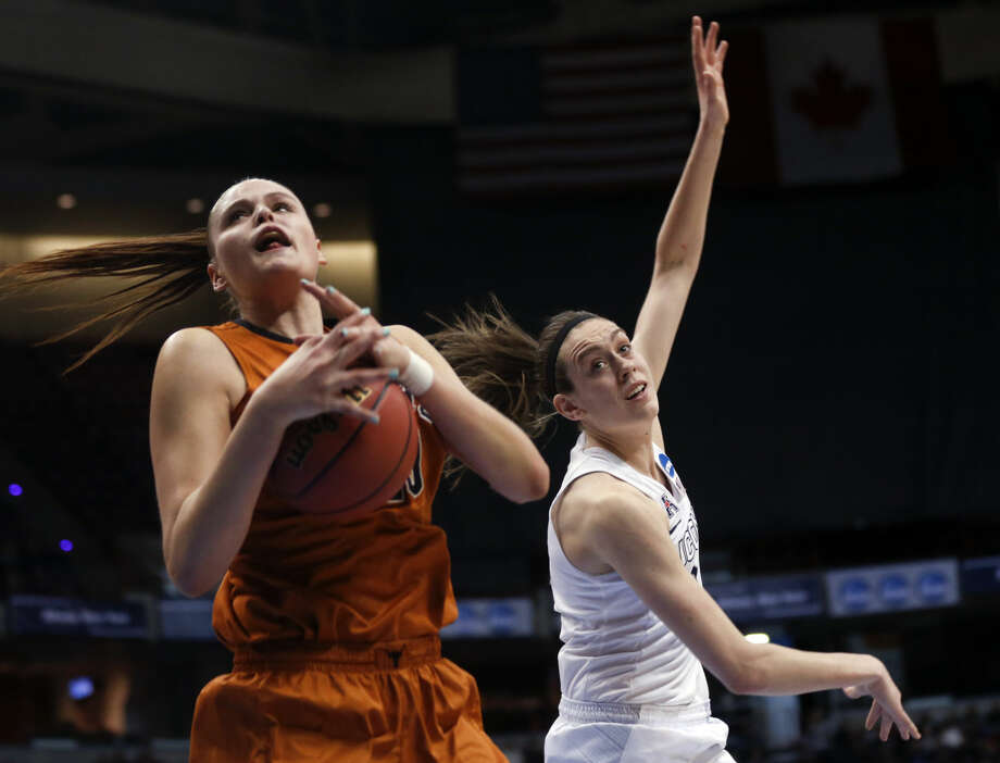Texas center Kelsey Lang, left, drives to the basket past Connecticut forward Breanna Stewart during the second half of a women's college basketball regional semifinal game in the NCAA Tournament on Saturday, March 28, 2015, in Albany, N.Y. (AP Photo/Mike Groll)