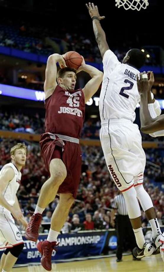Saint Joseph's Halil Kanacevic (45) passes away from Connecticut's DeAndre Daniels (2) during the first half of a second-round game in the NCAA college basketball tournament in Buffalo, N.Y., Thursday, March 20, 2014. (AP Photo/Nick LoVerde) / FR1171125 AP