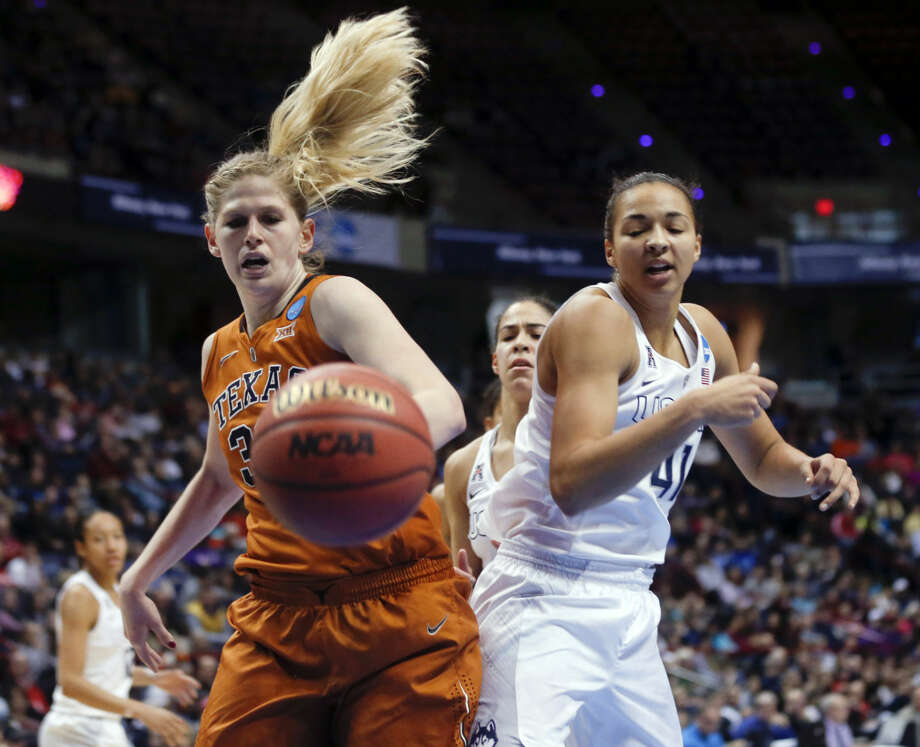 Texas forward Sara Hattis, left, and Connecticut center Kiah Stokes battle for the ball during the second half of a women's college basketball regional semifinal game in the NCAA Tournament on Saturday, March 28, 2015, in Albany, N.Y. UConn won 105-54. (AP Photo/Mike Groll)