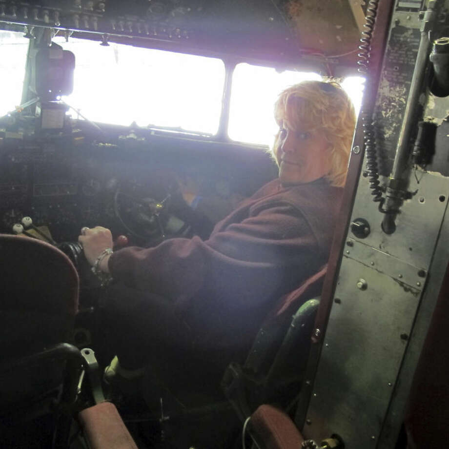 This photo taken March 6, 2014, shows pilot Naomi Wadsworth inside the cockpit of a World War II-era Douglas C-47, housed at the National Warplane Museum in Geneseo, N.Y. At the invitation of the French government, the airplane will return to France in June to participate in celebrations marking the 70th anniversary of the D-Day invasion of Normandy. The airplane, known as Whiskey 7 because of its markings, is one of the original troop carriers that dropped paratroopers in advance of the amphibious invasion. In June it will recreate its role and drop paratroopers over the original drop zone in Sainte-Mere-Eglise. (AP Photo/Carolyn Thompson)