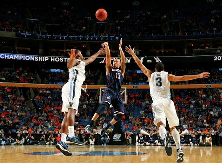 Villanova's Josh Hart (3) runs out to defend Connecticut's Shabazz Napier (13) during the second half of a third-round game in the NCAA men's college basketball tournament in Buffalo, N.Y., Saturday, March 22, 2014. (AP Photo/Bill Wippert) / FR170745 AP