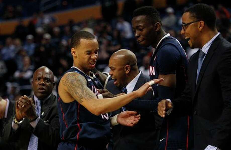 Connecticut guard Shabazz Napier (13) winces from a leg injury as he celebrates with assistant coaches and players late in the second half of a third-round game in the NCAA men's college basketball tournament in Buffalo, N.Y., Saturday, March 22, 2014. Connecticut defeated Villanova, 77-65. (AP Photo/Bill Wippert) / FR170745 AP