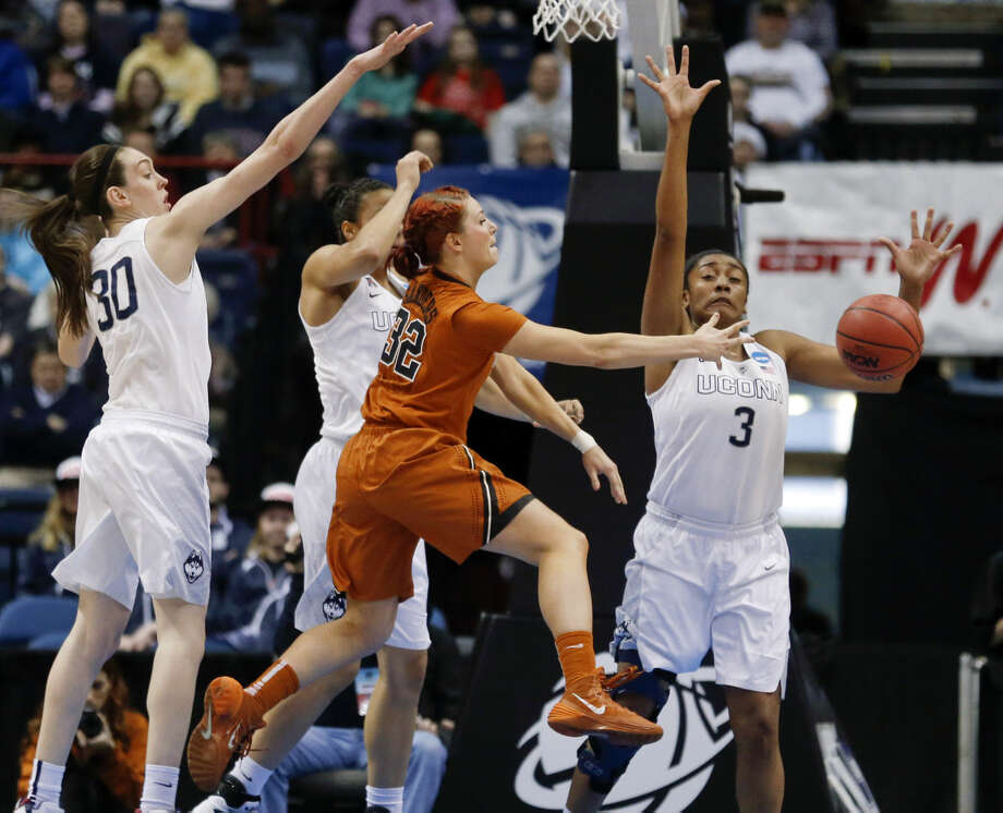Texas guard Brady Sanders (32) passes in front of Connecticut defenders Breanna Stewart (30), Kiah Stokes and Morgan Tuck (3) during the first half of a women's college basketball regional semifinal game in the NCAA Tournament on Saturday, March 28, 2015, in Albany, N.Y. (AP Photo/Mike Groll)