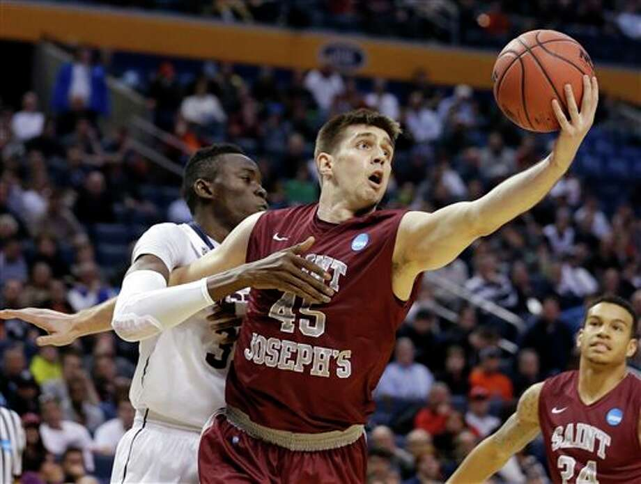Saint Joseph's Halil Kanacevic (45) rebounds the ball in front of Connecticut's Amida Brimah during the first half of a second-round game in the NCAA college basketball tournament in Buffalo, N.Y., Thursday, March 20, 2014. (AP Photo/Frank Franklin II) / AP