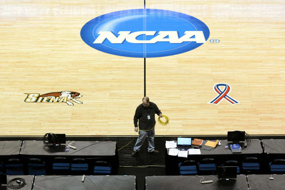 James Anilowski, an information technology professional, installs ethernet cables along radio radio row for broadcasters at the NCAA women's basketball tournament Thursday, March 26, 2015, at the Times Union Center in Albany, N.Y. Connecticut takes on Texas, and Dayton takes on Texas, in the regional semifinals on Saturday, March 28. (AP Photo/The Daily Gazette, (AP Photo/The Daily Gazette, Patrick Dodson) TROY, SCHENECTADY; SARATOGA SPRINGS; ALBANY AND AMSTERDAM OUT