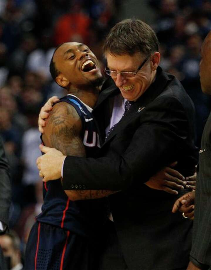 Connecticut guard Ryan Boatright (11) celebrates with assistant coach Glen Miller late in the second half of a third-round game in the NCAA men's college basketball tournament in Buffalo, N.Y., Saturday, March 22, 2014. Connecticut defeated Villanova, 77-65. (AP Photo/Bill Wippert) / FR170745 AP