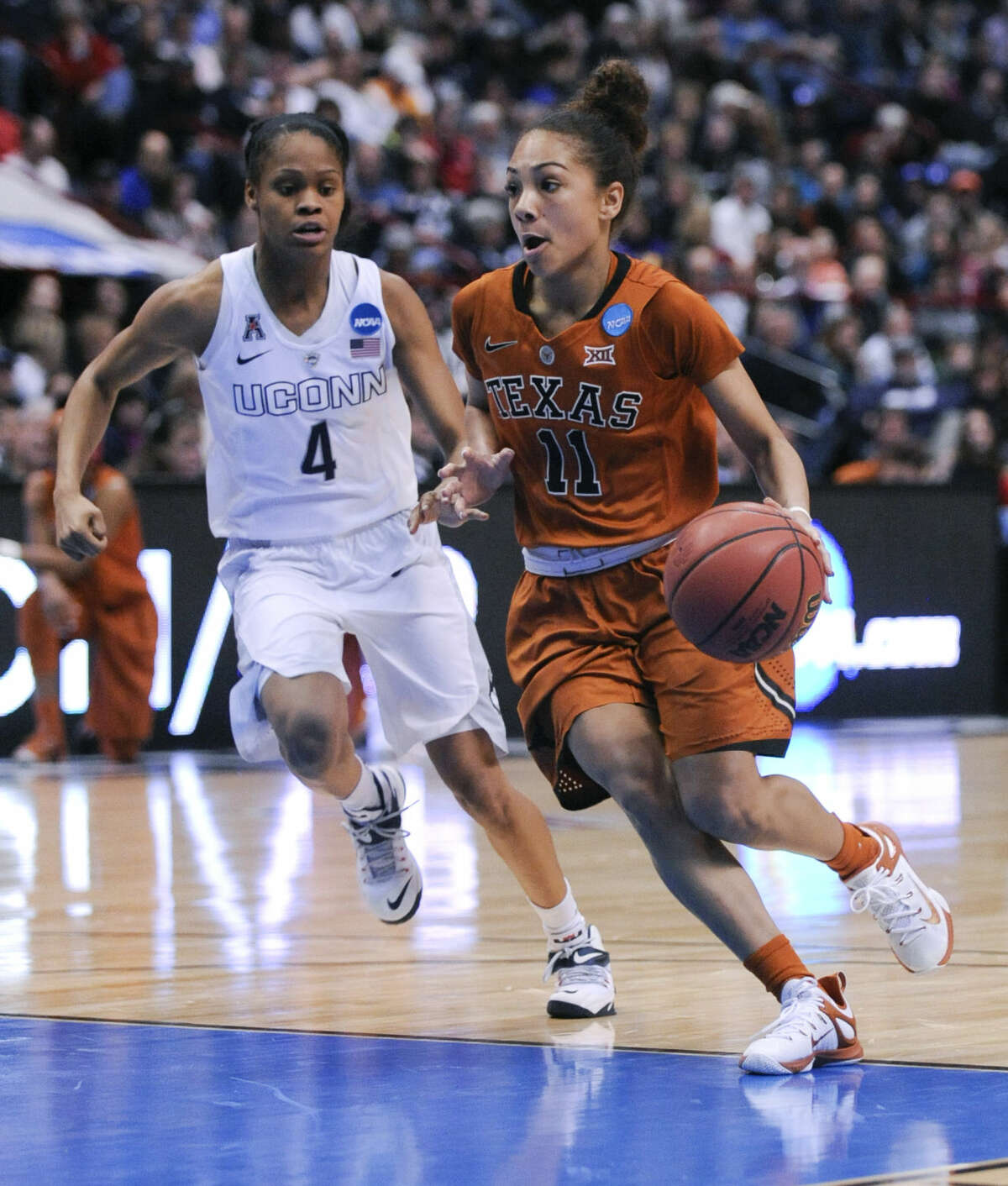 Texas guard Brooke McCarty (11) drives past Connecticut guard Moriah Jefferson (4) during the first half of a women's college basketball regional semifinal game in the NCAA Tournament on Saturday, March 28, 2015, in Albany, N.Y. (AP Photo/Tim Roske)