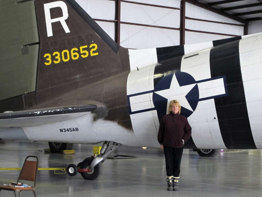 This photo taken March 6, 2014, shows pilot Naomi Wadsworth near a World War II-era Douglas C-47, housed at the National Warplane Museum in Geneseo, N.Y. At the invitation of the French government, the airplane will return to France in June to participate in celebrations marking the 70th anniversary of the D-Day invasion of Normandy. The airplane, known as Whiskey 7 because of its markings, is one of the original troop carriers that dropped paratroopers in advance of the amphibious invasion. In June it will recreate its role and drop paratroopers over the original drop zone in Sainte-Mere-Eglise. (AP Photo/Carolyn Thompson)