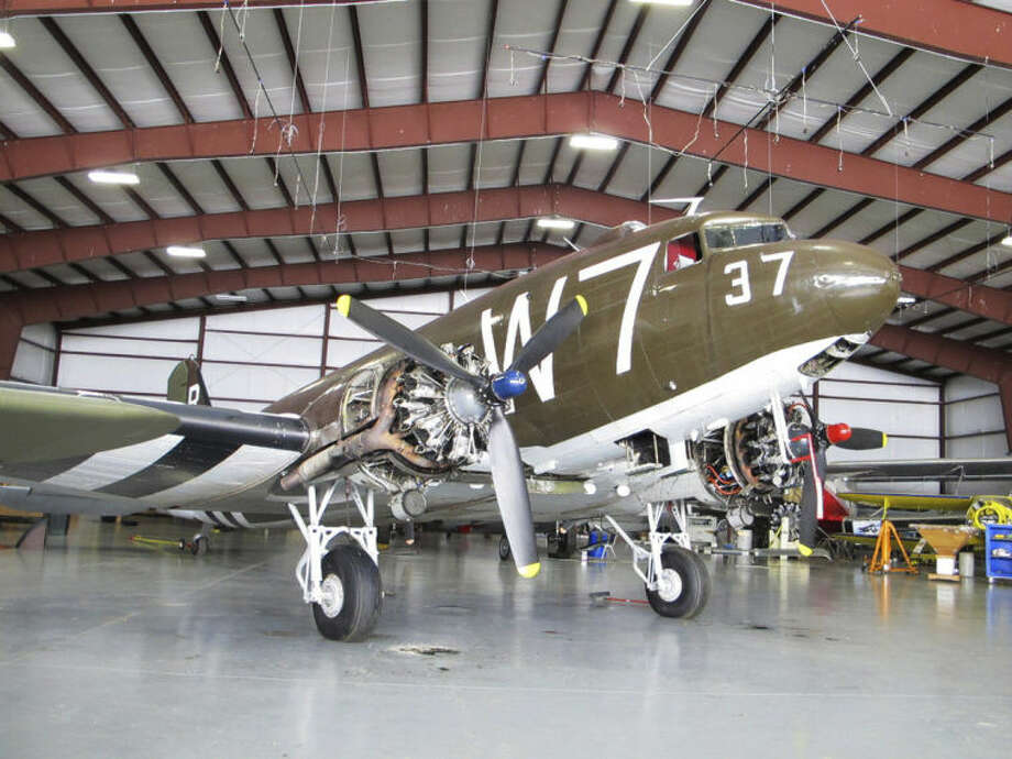 This photo taken March 6, 2014, shows a World War II-era Douglas C-47, housed at the National Warplane Museum in Geneseo, N.Y. At the invitation of the French government, the airplane will return to France in June to participate in celebrations marking the 70th anniversary of the D-Day invasion of Normandy. The airplane, known as Whiskey 7 because of its markings, is one of the original troop carriers that dropped paratroopers in advance of the amphibious invasion. In June it will recreate its role and drop paratroopers over the original drop zone in Sainte-Mere-Eglise. (AP Photo/Carolyn Thompson)