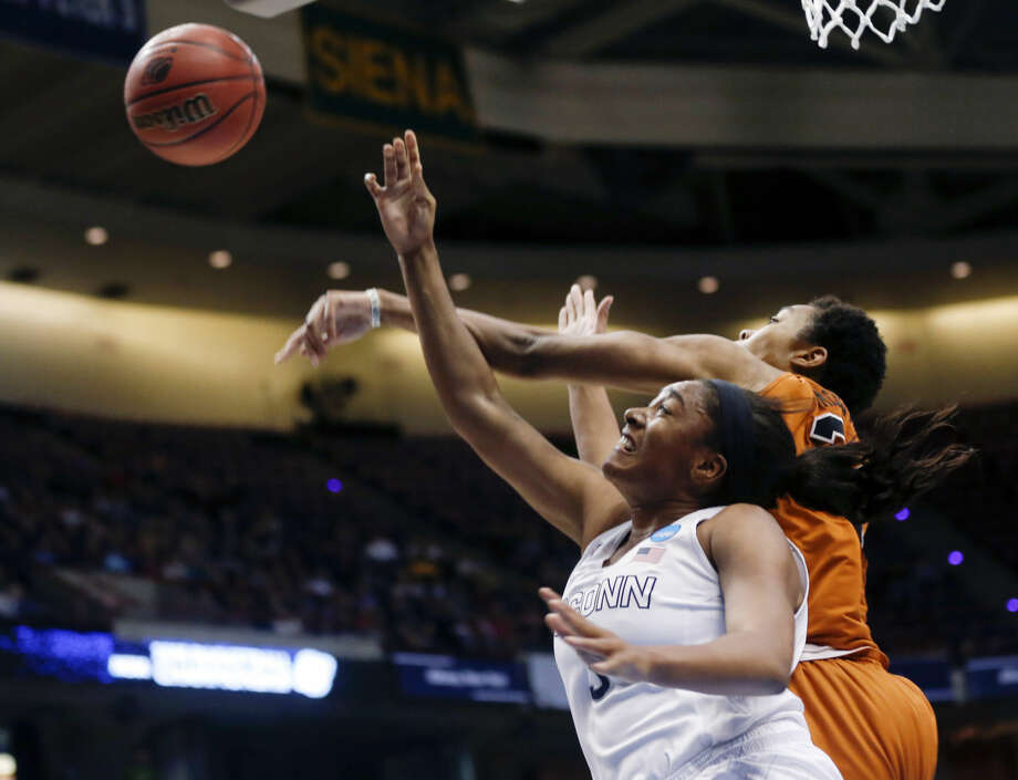 Texas center Imani McGee-Stafford, right, blocks a shot by Connecticut forward Morgan Tuck during the first half of a women's college basketball regional semifinal game in the NCAA Tournament on Saturday, March 28, 2015, in Albany, N.Y. (AP Photo/Mike Groll)