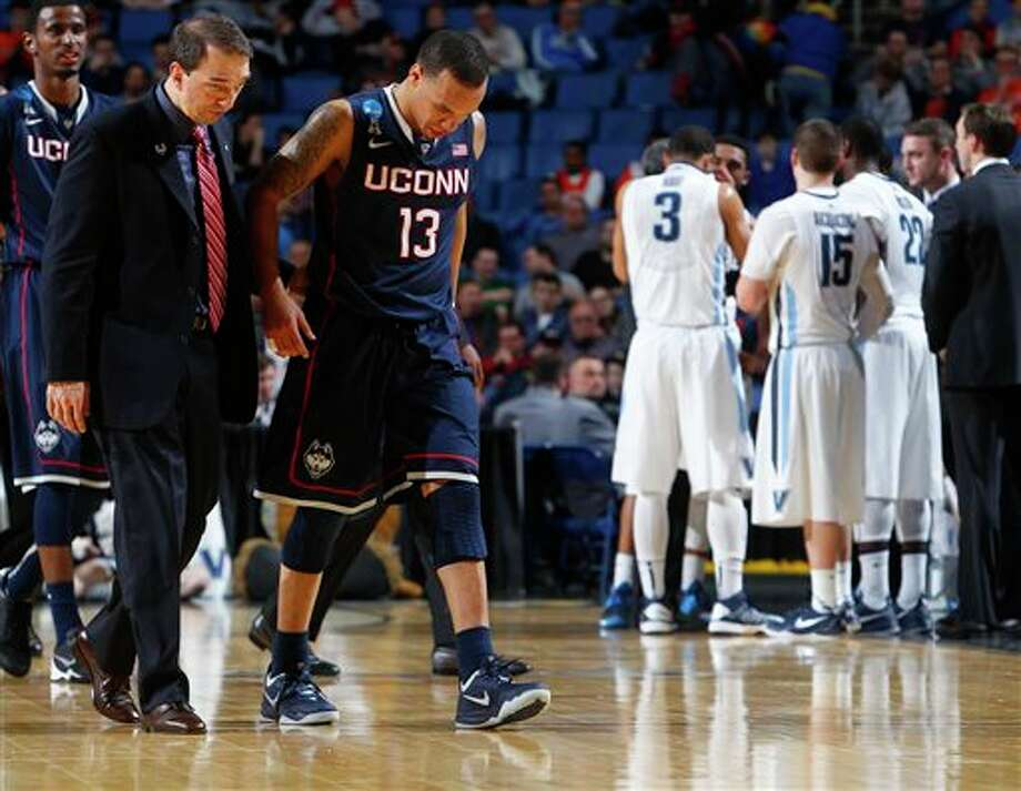 Connecticut's Shabazz Napier (13) is helped off the court after being hurt on a play during the second half of a third-round game against Villanova in the NCAA men's college basketball tournament in Buffalo, N.Y., Saturday, March 22, 2014. (AP Photo/Bill Wippert) / FR170745 AP