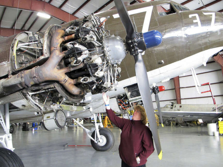 This photo taken March 6, 2014, shows pilot Naomi Wadsworth with a World War II-era Douglas C-47, housed at the National Warplane Museum in Geneseo, N.Y. At the invitation of the French government, the airplane will return to France in June to participate in celebrations marking the 70th anniversary of the D-Day invasion of Normandy. The airplane, known as Whiskey 7 because of its markings, is one of the original troop carriers that dropped paratroopers in advance of the amphibious invasion. In June it will recreate its role and drop paratroopers over the original drop zone in Sainte-Mere-Eglise. (AP Photo/Carolyn Thompson)