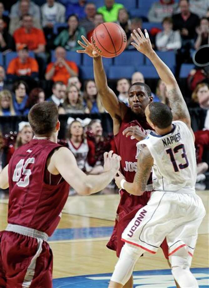 Saint Joseph's Ronald Roberts, Jr., center, passes the ball away from Connecticut's Shabazz Napier (13) to teammate Halil Kanacevic (45) during the first half of a second-round game in the NCAA college basketball tournament in Buffalo, N.Y., Thursday, March 20, 2014. (AP Photo/Bill Wippert) / FR170745 AP