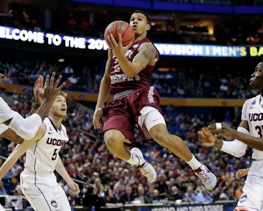 Saint Joseph's Chris Wilson, center, drives past Connecticut's Niels Giffey, left, during the first half of a second-round game in the NCAA college basketball tournament in Buffalo, N.Y., Thursday, March 20, 2014. (AP Photo/Nick LoVerde) / FR1171125 AP