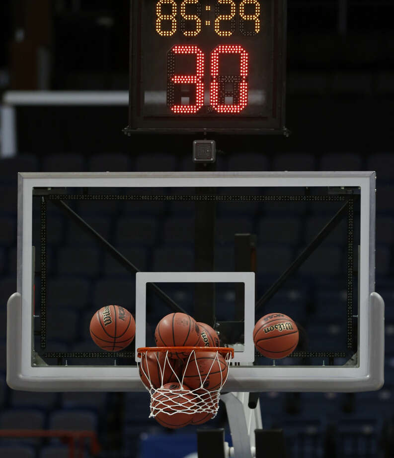Basketballs are stuck in a net as Connecticut practices for a women's college basketball regional semifinal game in the NCAA Tournament on Friday, March 27, 2015, in Albany, N.Y. UConn plays Texas on Saturday. (AP Photo/Mike Groll)