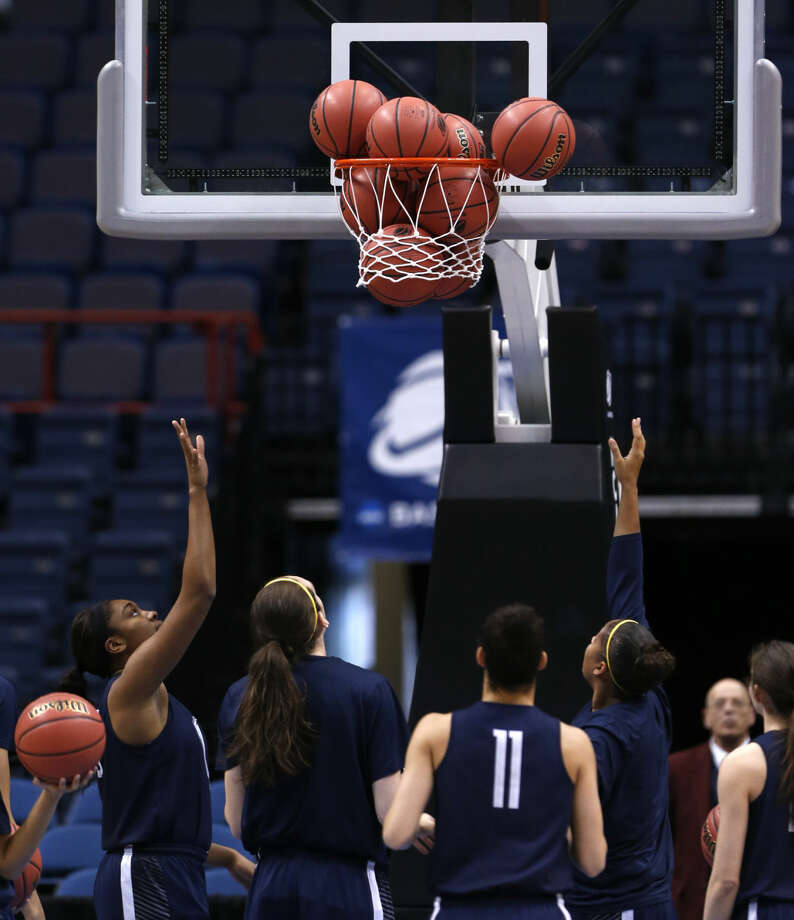 Connecticut players try to free basketballs that are caught in the net during practice for a women's college basketball regional semifinal game in the NCAA Tournament on Friday, March 27, 2015, in Albany, N.Y. UConn plays Texas on Saturday. (AP Photo/Mike Groll)