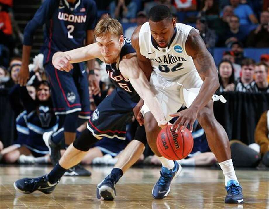 Connecticut's Niels Giffey (5) and Villanova's James Bell (32) reach for the loose ball during the second half of a third-round game in the NCAA men's college basketball tournament in Buffalo, N.Y., Saturday, March 22, 2014. (AP Photo/Bill Wippert) / FR170745 AP