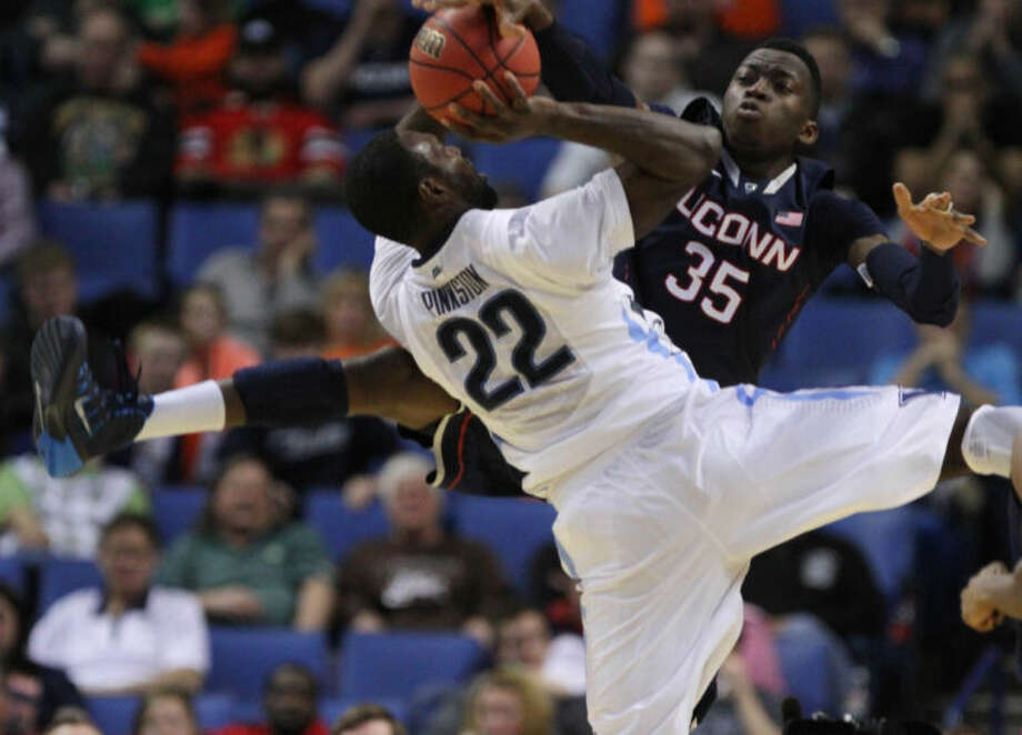 Villanova's JayVaughn Pinkston (22) is fouled by UConn's Amida Brimah (35) during the second half of the third-round game in the men's NCAA college basketball tournament at the First Niagara Center, Saturday, March 22, 2014. (AP Photo/The Buffalo News, Harry Scull Jr.)