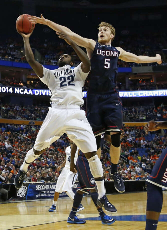 Villanova's JayVaughn Pinkston (22) drives past Connecticut's Niels Giffey (5) during the first half of a third-round game in the NCAA men's college basketball tournament in Buffalo, N.Y., Saturday, March 22, 2014. (AP Photo/Bill Wippert)