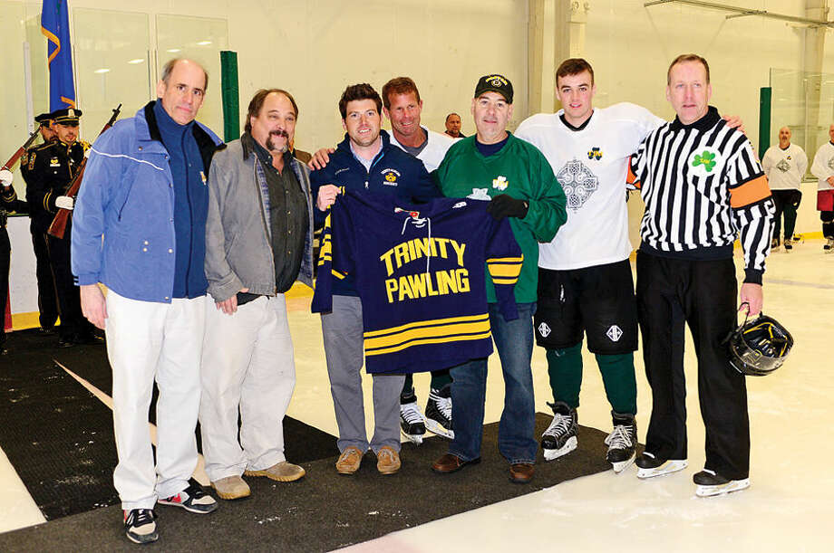 Hour photo / Erik Trautmann A group from Trinity Pawling hockey program honors retired NPD Lt. Timothy Murphy as the Norwalk PoliceUnion holds a benefit hockey game for Murphy Saturday at SoNo Ice House. Murphy was diagnosed with cancer shortly after retiring