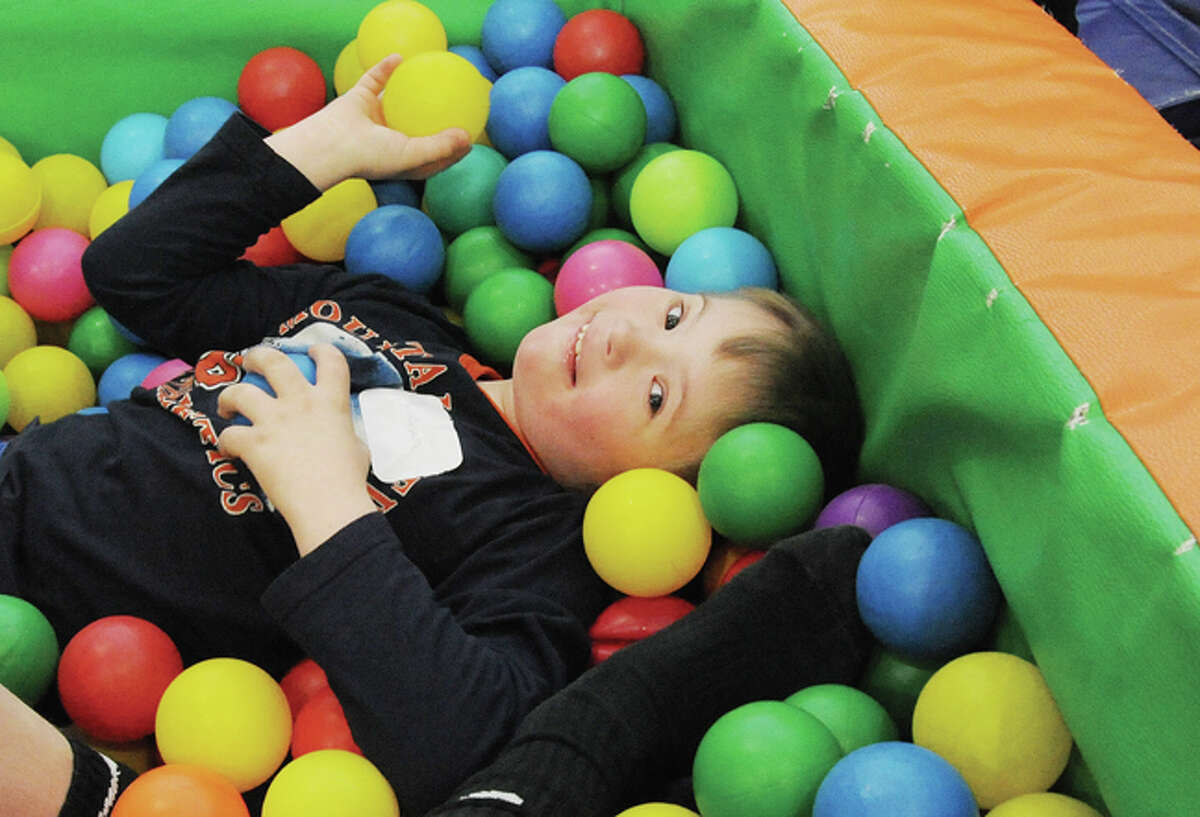 Aiden Piehl, 9, plays in the ball pit at the New Canaan YMCA for the fourth annual World Down Syndrome Day.