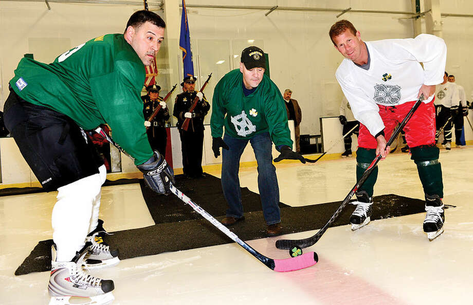 Hour photo / Erik Trautmann Sgt. Mark Lepore and Kyle Benson stand ready as recently retired NPD Lt. Timothy Murphy performs a ceremonial puck drop as the Norwalk Police Union holds benefit hockey game for Murphy Saturday at SoNo Ice House.