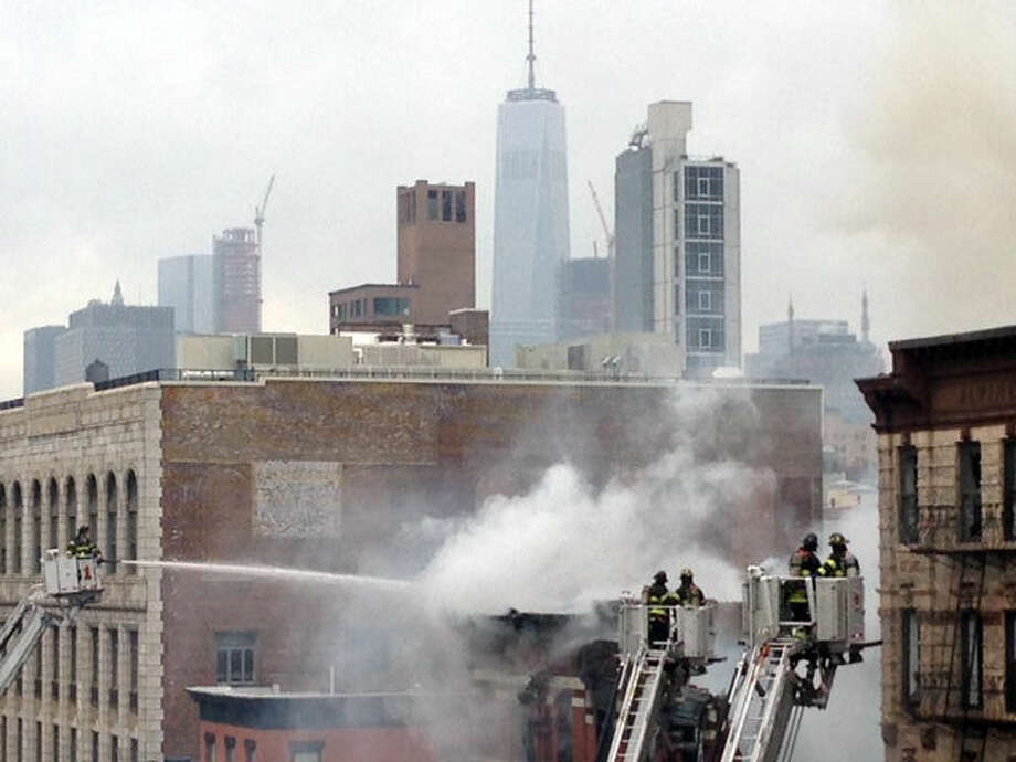 New York City firefighters work the scene of a large fire and building collapse near New York University, Thursday, March 26, 2015 in New York, and at least two people were critically injured, firefighters said. Orange flames and black smoke billowed from the facade and roof of the five-story building in Manhattan, near several NYU buildings and the Washington Square Park area. Flames were spreading to other buildings. (AP Photo/Tom Hays)