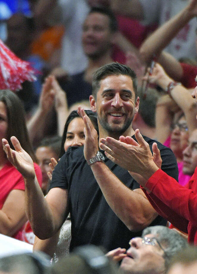 Aaron Rodgers, quarterback for the Green Bay Packers NFL football team, cheers during the second half of a college basketball regional final between Wisconsin and Arizona in the NCAA Tournament, Saturday, March 28, 2015, in Los Angeles. (AP Photo/Mark J. Terrill)