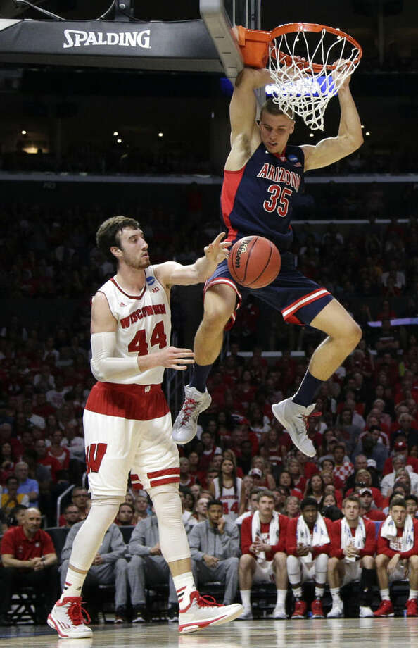 Arizona center Kaleb Tarczewski (35) dunks over Wisconsin forward Frank Kaminsky (44) during the first half of a college basketball regional final in the NCAA Tournament, Saturday, March 28, 2015, in Los Angeles. (AP Photo/Jae C. Hong)