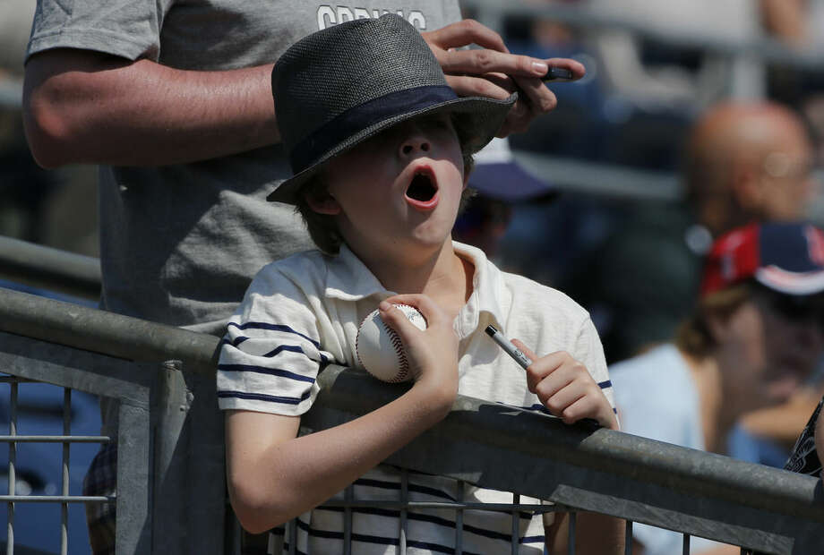 New York Yankees fan, William Jeffries, of Little Rock, Ark., yawns while he waits for any of the Yankees to sign his baseball before an exhibition spring training baseball game against the Tampa Bay Rays, Thursday, March 26, 2015, in Port Charlotte, Fla. The Rays won 6-5. (AP Photo/Brynn Anderson)