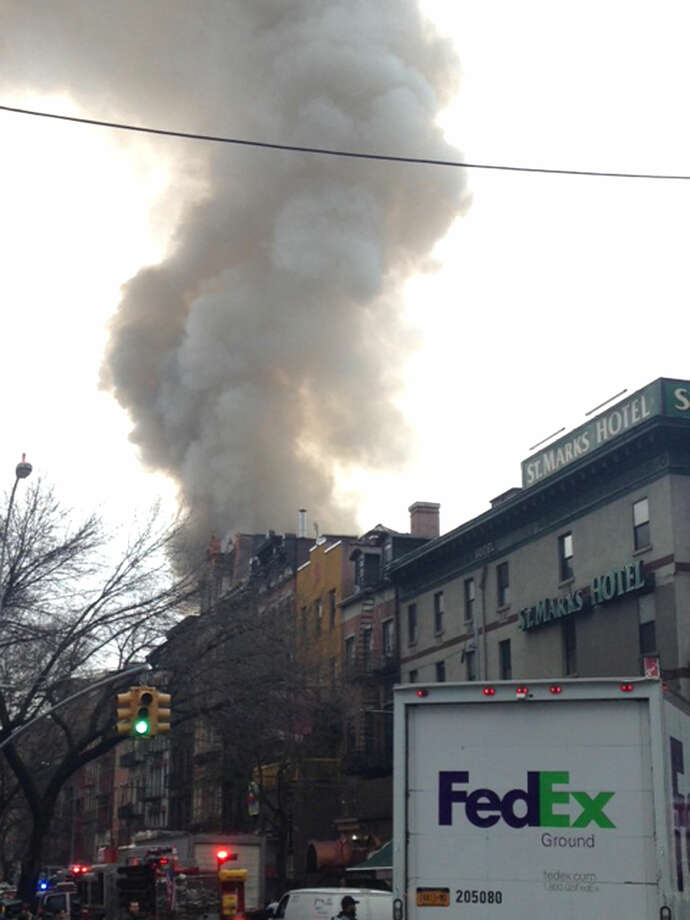 Smoke billows from a building in New York's East Village neighborhood at the scene of a large fire and a partial building collapse. (AP Photo/Jonathan Lemire)