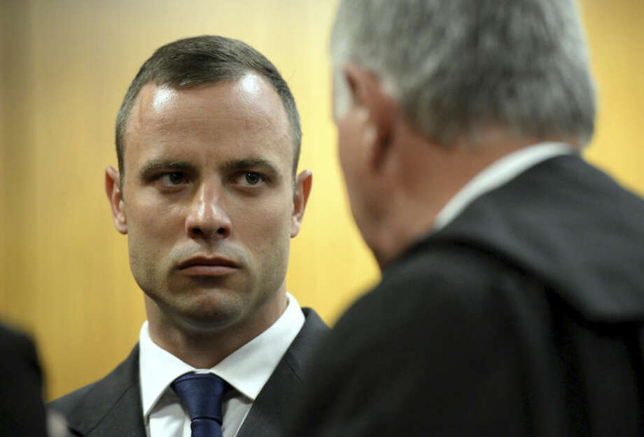Oscar Pistorius talks to to his defense attorney Barry Roux before the proceedings get under way at the high court in Pretoria, South Africa, Monday, March 24, 2014. The trial of Pistorius, who is charged with murder for the shooting death of his girlfriend Reeva Steenkamp on Valentines Day in 2013, is beginning its fourth week. (AP Photo/Chris Collingridge, Pool)