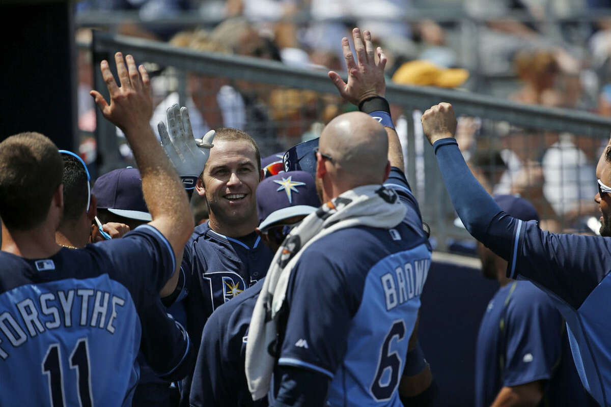 Tampa Bay Rays Evan Longoria, center, high-fives his teammates after scoring a run in the second inning during an exhibition spring training baseball game against the New York Yankees, Thursday, March 26, 2015, in Port Charlotte, Fla. The Rays won 6-5. (AP Photo/Brynn Anderson)