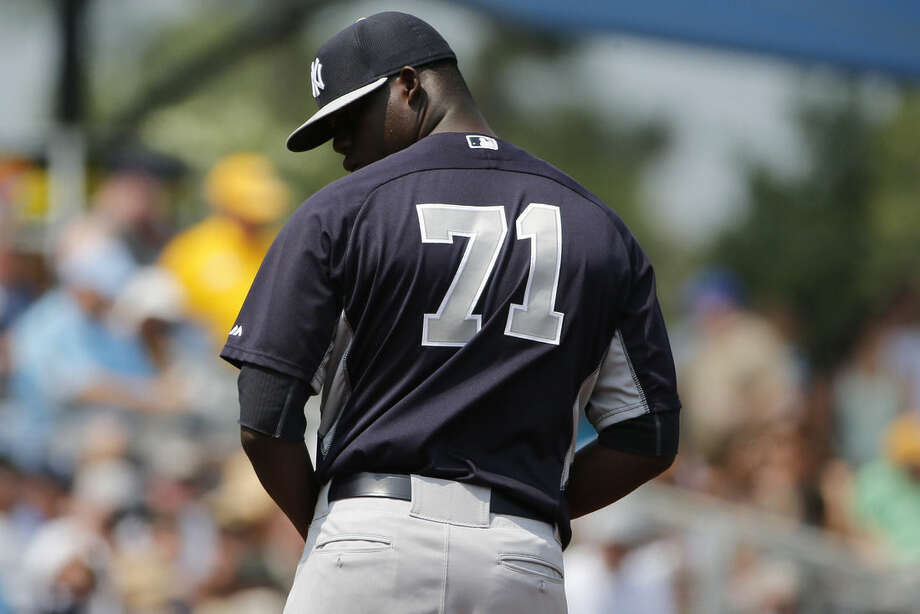 New York Yankees relief pitcher Jose Ramirez peers over his shoulder at a first base runner in the fifth inning during an exhibition spring training baseball game against the Tampa Bay Rays, Thursday, March 26, 2015, in Port Charlotte, Fla. The Rays won 6-5. (AP Photo/Brynn Anderson)