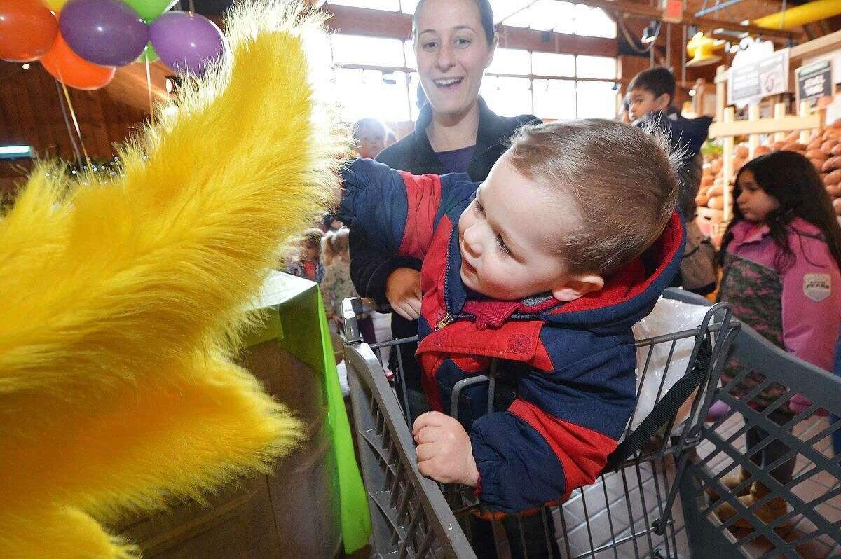 Hour Photo/Alex von Kleydorff 2yr old Ryan Strype with mom Kristen gets a high five and an egg from Daphne the Duck during Stew Leonard's easter egg hunt Eggs-travaganza