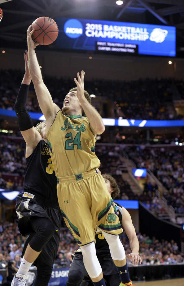 Notre Dame's Pat Connaughton (24) shoots as Wichita State's Ron Baker defends during the first half of a college basketball game in the NCAA men's tournament regional semifinals, Thursday, March 26, 2015, in Cleveland. (AP Photo/David Richard)