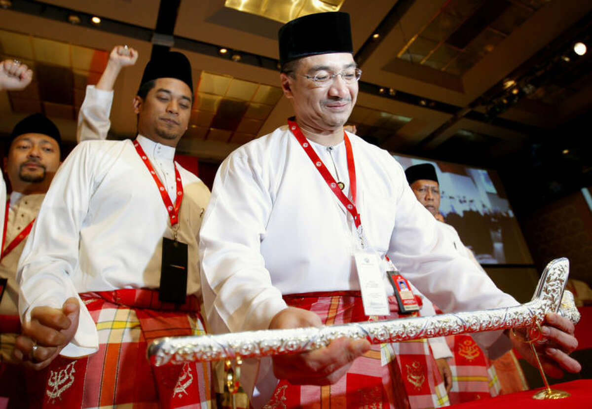 FILE - In this Wednesday, March 25, 2009 file photo, Hishammuddin Hussein, front, chief of Youth wings placing the