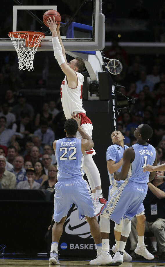 Wisconsin's Sam Dekker dunks over North Carolina's Isaiah Hicks (22), Marcus Paige, center, and Theo Pinson (1) during the first half of a college basketball regional semifinal in the NCAA Tournament, Thursday, March 26, 2015, in Los Angeles. (AP Photo/Jae C. Hong)