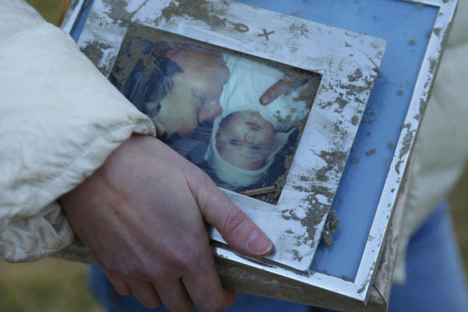 A woman holds family photos pulled from the rubble at the site of Saturday's fatal mudslide near Oso, Wash., Sunday, March 23, 2014. (AP Photo /The Herald, Genna Martin)