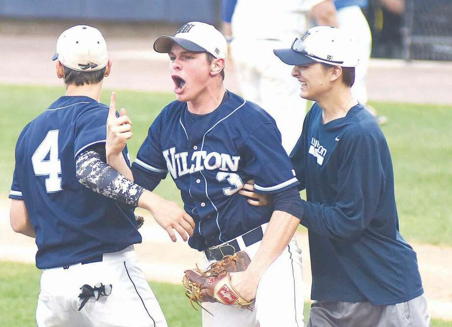 Wilton starting pitcher Jackson Ward, center, signals that his team needs one more win to earn the FCIAC championship after earning a 5-1 win over Darien in the league semifinals at The Ballpark at Harbor Yard on Wednesday. Ward struck out 11 and walked one in a complete-game win.