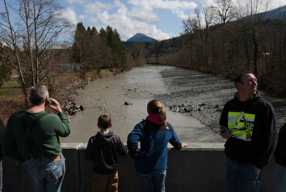 Residents watch as debris comes down the Stillaguamish River from the Whitman Road bridge east of Oso Sunday, March 23, 2014. (AP Photo /The Herald, Mark Mulligan)