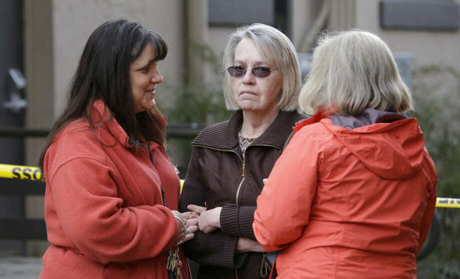 Barbara Welsh, center, whose husband is missing in a deadly mudslide, stands with relatives Monday, March 24, 2014, in Arlington, Wash. The search for survivors of the deadly mudslide grew Monday to include 108 names of people who were reported missing or were unaccounted for, but authorities cautioned the figure would likely decline dramatically. The size of the list raised concerns the death toll would rise far above the eight people who have been confirmed dead after the 1-square-mile (2.6-square-kilometer) slide Saturday swept through part of a former fishing village about 55 miles (80 miles) northeast of Seattle. Several people also were critically injured. About 30 homes were destroyed, and the debris blocked a 1-mile (1.6 kilometer) stretch of state highway. (AP Photo/Elaine Thompson)