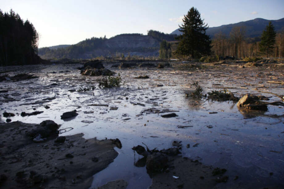 Water and mud back up on the east side of Saturday's fatal mudslide near Oso, Wash., Sunday March 23, 2014. (AP Photo /The Herald, Genna Martin)
