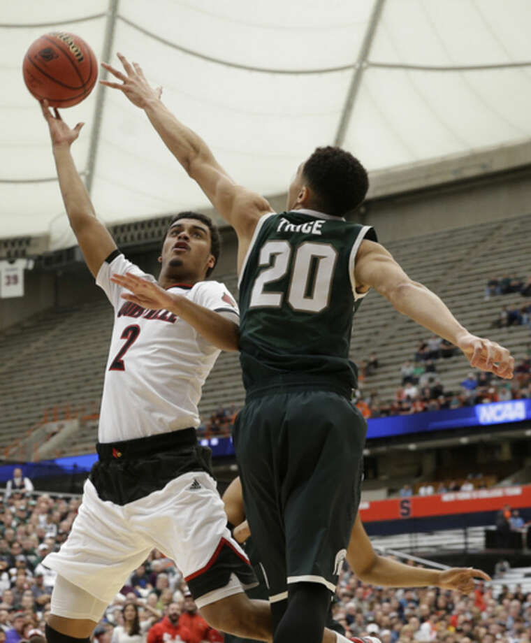 Louisville's Quentin Snider (2) drives past Michigan State's Travis Trice (20) during the first half of a regional final in the NCAA men's college basketball tournament Sunday, March 29, 2015, in Syracuse, N.Y. (AP Photo/Seth Wenig)