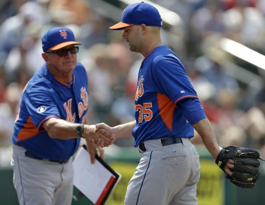 New York Mets pitching coach Dan Warthen, left, congratulates pitcher Dillon Gee (35) after he was pulled in the sixth inning of an exhibition baseball game against the Minnesota Twins in Fort Myers, Fla., Friday, March 21, 2014. (AP Photo/Gerald Herbert)