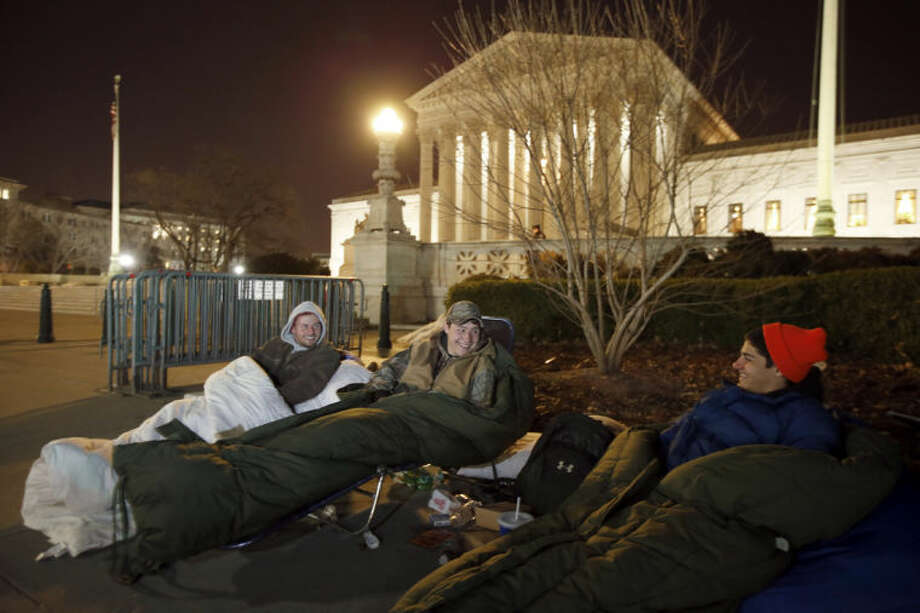 Brandon, left, from Warrenton, Va., sits with Matt and Zack, both from Nokesville, Va., as they wait in line in front of the Supreme Court, Monday, March 24, 2014, in Washington. The men arrived Friday afternoon to be first in line. The Supreme Court is weighing whether corporations have religious rights that exempt them from part of the new health care law that requires coverage of birth control for employees at no extra charge. (AP Photo/Alex Brandon)
