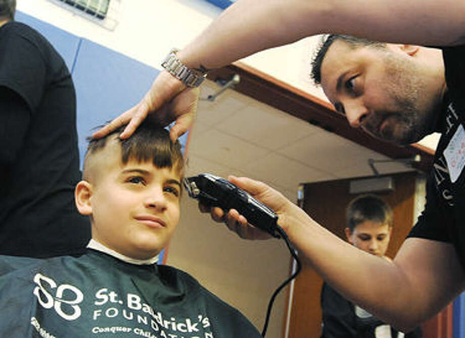 Ben Seideman 10, gets his head shaved by Gregory Mahoney with Austin-Rolfe Salon out of Westport. The 11th annual TeamBrent St. Baldrick's Celebration was held at the Wesprt Weston YMCA in Westport on Sunday. Hour photo/Matthew Vinci