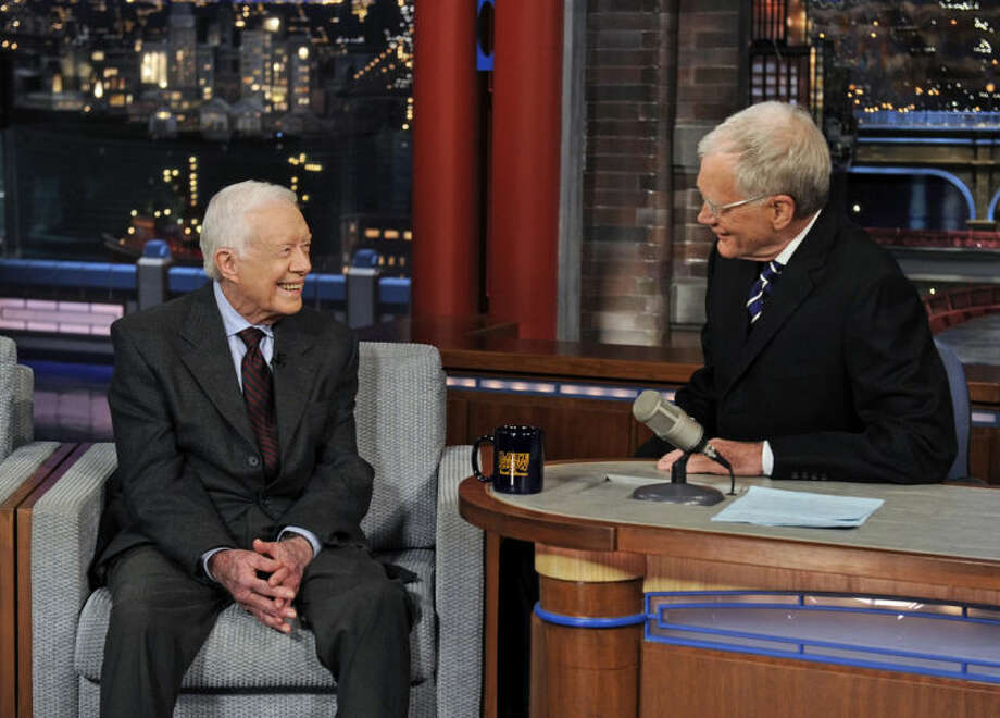 "In this photo provided by CBS, former President Jimmy Carter, left, talks with David Letterman on ""Late Show with David Letterman,"" Monday March 24, 2014. Carter said during the broadcast that the Crimean annexation was ""inevitable"" because Russia considers it to be part of their country and so many Crimeans consider themselves Russian. But he says Russian President Vladimir Putin shouldn't be permitted to go any further. (AP Photo/CBS, Jeffrey R. Staab)"